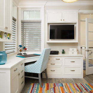 Study room - beach style built-in desk medium tone wood floor and brown floor study room idea in Grand Rapids with white walls
