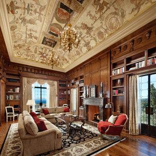 Foto di un ampio studio mediterraneo con parquet scuro, camino classico e scrivania incassata