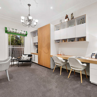 Inspiration for a mid-sized contemporary study room in Melbourne with white walls, carpet, a built-in desk and grey floor.