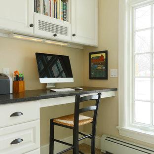他の地域の小さいトランジショナルスタイルのおしゃれな書斎 (黄色い壁、ライムストーンの床、暖炉なし、造り付け机) の写真