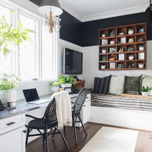Inredning av ett klassiskt arbetsrum, med svarta väggar, mörkt trägolv, ett inbyggt skrivbord och brunt golv