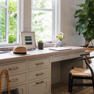 Modelo de despacho tradicional renovado, grande, con paredes grises, suelo de madera en tonos medios, escritorio empotrado y suelo marrón