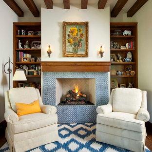 Foto de despacho mediterráneo con paredes blancas, suelo de madera en tonos medios, chimenea tradicional, marco de chimenea de baldosas y/o azulejos y escritorio independiente