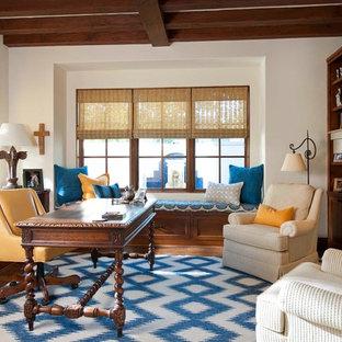 Medelhavsstil inredning av ett hemmabibliotek, med vita väggar, mellanmörkt trägolv, en standard öppen spis, en spiselkrans i trä och ett fristående skrivbord