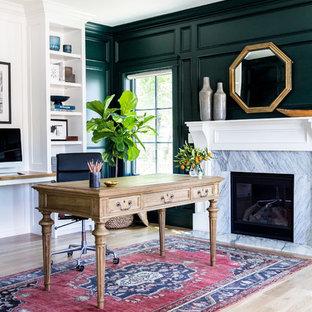 Стильный дизайн: рабочее место в классическом стиле с зелеными стенами, светлым паркетным полом, стандартным камином, фасадом камина из камня и отдельно стоящим рабочим столом - последний тренд