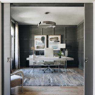 Inredning av ett modernt mellanstort arbetsrum, med grå väggar, ljust trägolv, ett fristående skrivbord och beiget golv