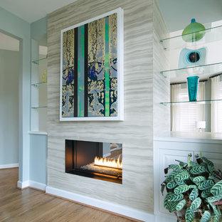 Idee per un ufficio minimal di medie dimensioni con pareti blu, pavimento in legno massello medio, camino lineare Ribbon, scrivania autoportante e pavimento marrone