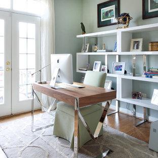 Modelo de despacho contemporáneo, de tamaño medio, con paredes azules, suelo de madera en tonos medios, escritorio independiente, chimenea de doble cara y suelo marrón