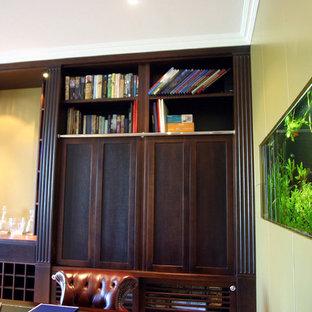 クライストチャーチのトラディショナルスタイルのおしゃれなホームオフィス・書斎 (ライブラリー、カーペット敷き、標準型暖炉、木材の暖炉まわり、自立型机、ベージュの床) の写真