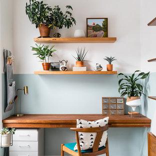 Foto på ett tropiskt arbetsrum, med blå väggar, mellanmörkt trägolv, ett inbyggt skrivbord och brunt golv