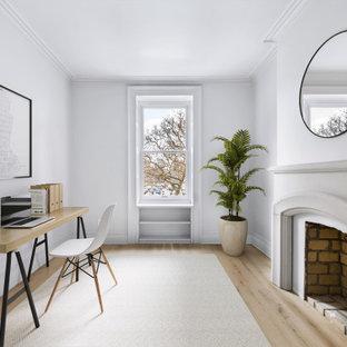 ニューヨークの中くらいのトランジショナルスタイルのおしゃれなアトリエ・スタジオ (グレーの壁、淡色無垢フローリング、標準型暖炉、コンクリートの暖炉まわり、自立型机、ベージュの床) の写真