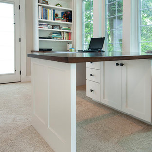 Ispirazione per un ufficio stile americano di medie dimensioni con pareti beige, moquette, camino classico, cornice del camino in pietra, scrivania incassata e pavimento beige