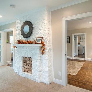 Foto de despacho de estilo americano, de tamaño medio, con paredes beige, moqueta, chimenea tradicional, marco de chimenea de piedra, escritorio empotrado y suelo beige