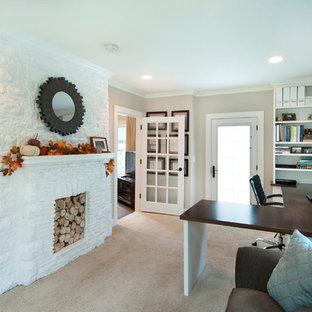 Idee per un ufficio stile americano di medie dimensioni con pareti beige, moquette, camino classico, cornice del camino in pietra, scrivania incassata e pavimento beige