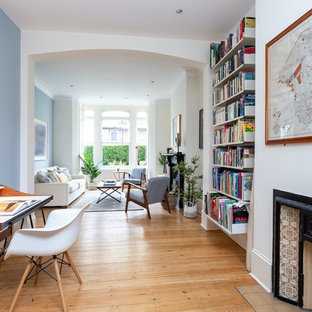 Inspiration for a traditional home office and library in London with white walls, medium hardwood flooring, a two-sided fireplace, a freestanding desk and brown floors.