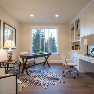 Réalisation d'un bureau champêtre avec un mur beige, un sol en bois foncé et un bureau intégré.