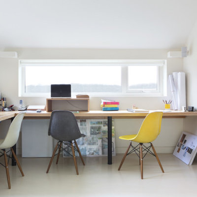 Large trendy built-in desk white floor study room photo in Oxfordshire with white walls