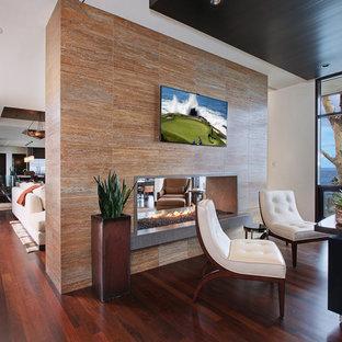 オレンジカウンティの広いコンテンポラリースタイルのおしゃれな書斎 (ベージュの壁、濃色無垢フローリング、両方向型暖炉、タイルの暖炉まわり、自立型机、茶色い床) の写真