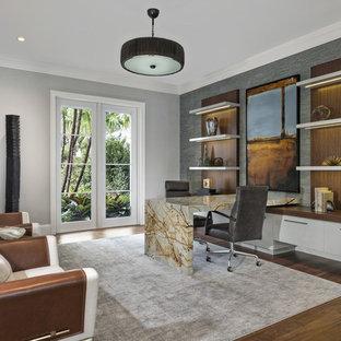 Diseño de despacho contemporáneo, extra grande, con paredes grises, escritorio empotrado, suelo de madera en tonos medios y suelo marrón
