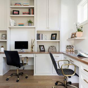Exemple d'un bureau bord de mer de taille moyenne avec un mur blanc, un sol en bois brun, un bureau intégré et un sol marron.