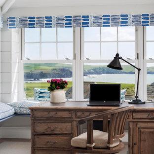 Bild på ett stort maritimt hemmastudio, med vita väggar, mellanmörkt trägolv, ett fristående skrivbord och brunt golv