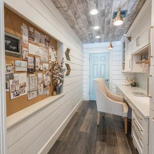 Foto på ett litet lantligt hemmabibliotek, med vita väggar, vinylgolv, ett inbyggt skrivbord och brunt golv