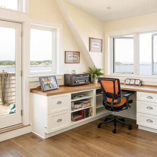 На фото: рабочее место в морском стиле с паркетным полом среднего тона, встроенным рабочим столом и бежевыми стенами