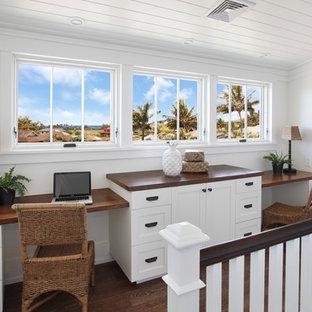 Idee per uno studio tropicale con pareti bianche, pavimento in legno massello medio, scrivania incassata e pavimento marrone