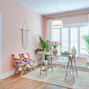 Exotisk inredning av ett mellanstort hemmabibliotek, med rosa väggar, mellanmörkt trägolv, ett fristående skrivbord och brunt golv