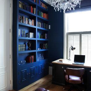 Aménagement d'un bureau victorien avec un mur bleu, un sol en bois brun et un bureau indépendant.