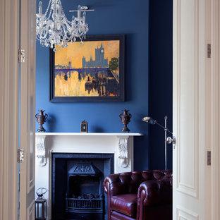 Foto di uno studio vittoriano con pareti blu, pavimento in legno massello medio e camino classico
