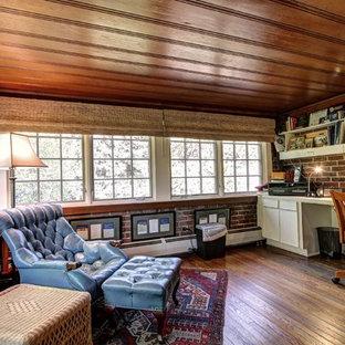 デンバーの大きいカントリー風おしゃれな書斎 (濃色無垢フローリング、暖炉なし、造り付け机、茶色い床、赤い壁) の写真