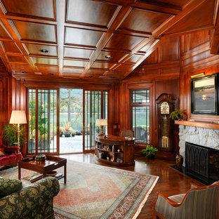Inspiration för mycket stora klassiska hemmabibliotek, med mörkt trägolv, en standard öppen spis, en spiselkrans i sten, ett fristående skrivbord och bruna väggar
