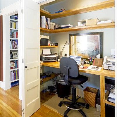 Elegant built-in desk medium tone wood floor home office photo in San Francisco with gray walls