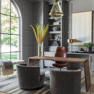Diseño de despacho tradicional renovado, sin chimenea, con paredes grises, suelo de madera clara, escritorio independiente y suelo marrón