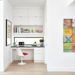 トロントの小さいミッドセンチュリースタイルのおしゃれな書斎 (白い壁、淡色無垢フローリング、暖炉なし、造り付け机、ベージュの床) の写真