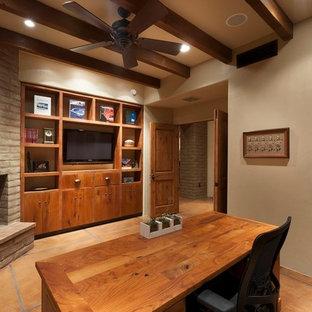 Immagine di un grande ufficio classico con pareti beige, scrivania autoportante, pavimento in cemento, camino ad angolo e cornice del camino in mattoni