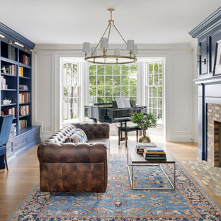ミネアポリスのビーチスタイルのおしゃれなホームオフィス・書斎 (ライブラリー、青い壁、標準型暖炉、レンガの暖炉まわり、造り付け机、淡色無垢フローリング) の写真