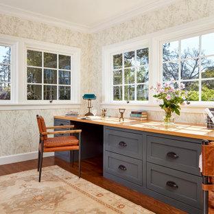 Inspiration pour un bureau traditionnel avec un mur beige, un sol en bois brun, un bureau intégré, un sol marron et du papier peint.