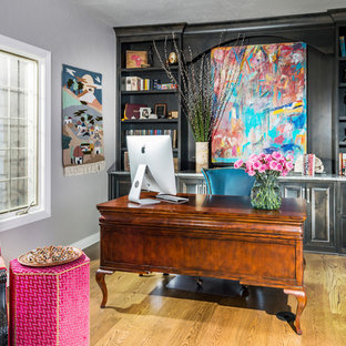 Photo of a mid-sized eclectic study room in Other with a freestanding desk, grey walls, medium hardwood floors and brown floor.