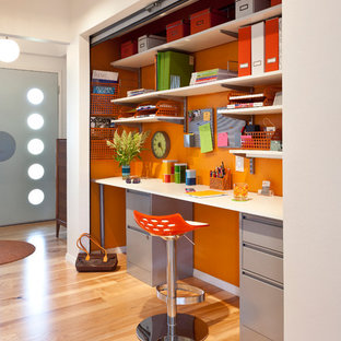 Inspiration for a 1950s built-in desk medium tone wood floor home office remodel in Other with orange walls