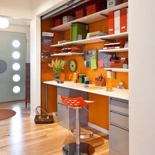 Стильный дизайн: кабинет в стиле ретро с оранжевыми стенами, паркетным полом среднего тона и встроенным рабочим столом - последний тренд