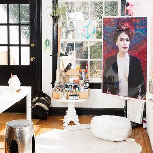 Ejemplo de estudio ecléctico, pequeño, con paredes blancas, suelo de madera clara, escritorio independiente y suelo marrón