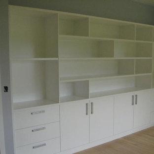 Ejemplo de despacho contemporáneo, grande, con paredes azules, suelo de madera clara y suelo rosa