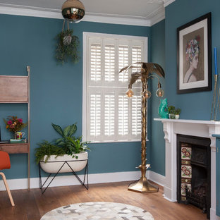 Idéer för att renovera ett mellanstort eklektiskt hemmabibliotek, med blå väggar, brunt golv, mörkt trägolv, en standard öppen spis och ett fristående skrivbord