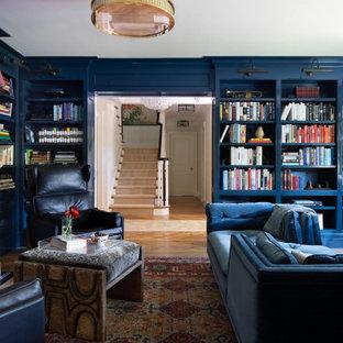 Foto di un grande studio chic con pareti nere, pavimento in legno massello medio, libreria, camino classico, cornice del camino in cemento e pavimento beige
