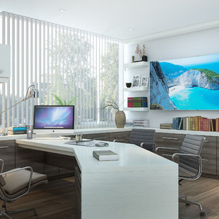 This is an example of a large modern home office and library in Los Angeles with white walls, medium hardwood flooring, a built-in desk and brown floors.