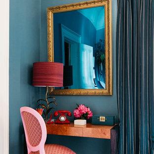 Immagine di un piccolo studio design con libreria, pareti verdi, moquette, camino classico, cornice del camino in pietra, scrivania autoportante e pavimento rosa
