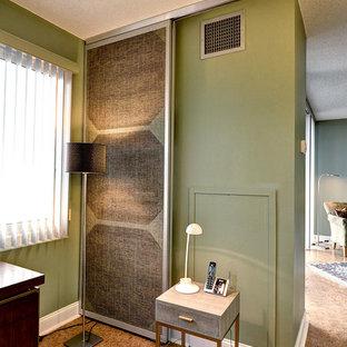 Bild på ett mellanstort funkis hemmabibliotek, med gröna väggar, korkgolv och ett fristående skrivbord