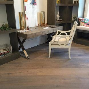 Inspiration för ett litet rustikt hemmabibliotek, med vita väggar, mellanmörkt trägolv, ett fristående skrivbord och brunt golv